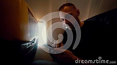 El hombre atractivo joven utiliza smartphone dentro del aeroplano al lado de ventana El viajar masculino hermoso por el aire almacen de video