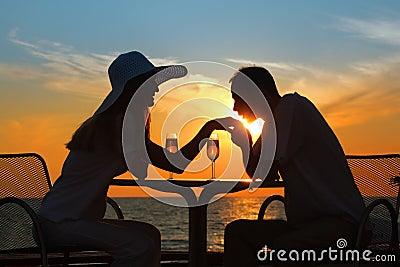 El hombre besa la mano a la mujer en puesta del sol afuera