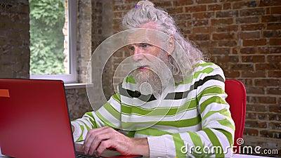 El hombre caucásico envejecido melenudo impresionante con la barba blanca larga es que mecanografía y de demostración de gesto qu almacen de video