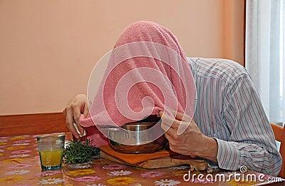 El hombre con la toalla rosada respira los vapores del bálsamo para tratar fríos y gripe