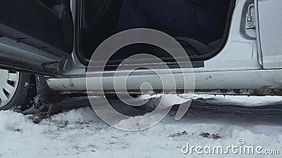 El hombre conductor no se lavó las piernas de la nieve y se subió al auto en invierno Tiempo malo y frío Movimiento lento en almacen de metraje de vídeo