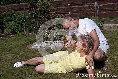 El hombre da a mujer con el agotamiento de calor algo beber