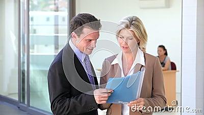 El hombre de negocios And Businesswoman Meet y discute informe almacen de metraje de vídeo