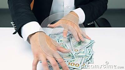 El hombre de negocios irreconocible codicioso da la porción que ase de cientos billetes de dólar almacen de metraje de vídeo