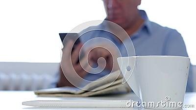 El hombre de negocios In Office Room toma una pausa y un texto del trabajo usando un teléfono móvil almacen de video