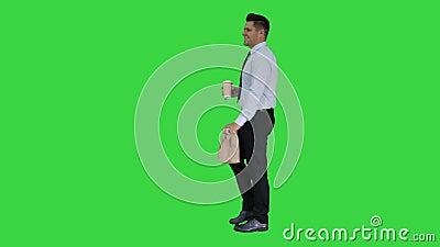 El hombre de negocios que camina con se lleva la bolsa del caf? y de papel con el almuerzo en una pantalla verde, llave de la cro almacen de video