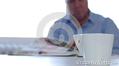 El hombre de negocios relajado en un d?a de la ma?ana goza de un peri?dico sabroso de la lectura del caf? almacen de metraje de vídeo