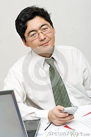 El hombre de negocios sonriente sostiene su móvil