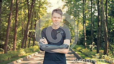El hombre discapacitado con la prótesis biónica se coloca, cruzando sus manos Ser humano con un brazo del robot metrajes