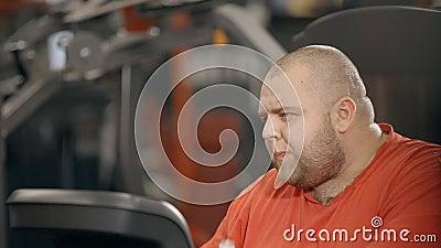 El hombre gordo rechoncho está sosteniendo la botella de agua y está bebiendo para poca rotura entre el entrenamiento agotado pes almacen de video