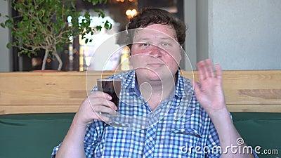 El hombre gordo sostiene un vidrio de cola de la bebida en café y el saludo, decir hola agitando la mano almacen de metraje de vídeo