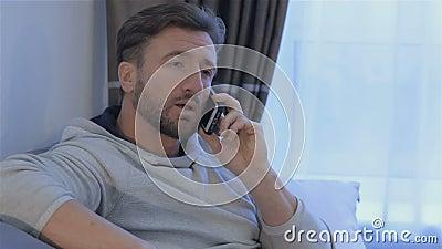 El hombre habla en el teléfono en casa almacen de video