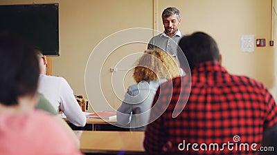 El hombre hermoso del alto profesor de escuela está hablando con los estudiantes que se están sentando en las tablas en sala de c metrajes