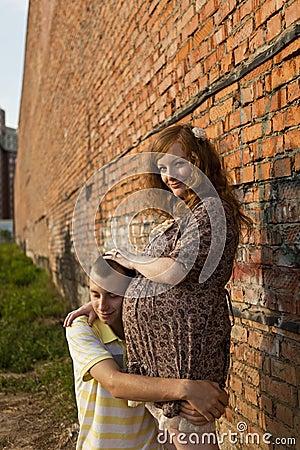 El hombre joven besa a su esposa embarazada