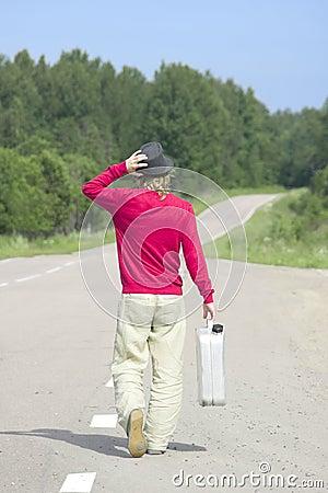 El hombre joven que recorre abajo de la carretera con el gas vacío puede