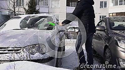 El hombre limpia un parabrisas o parabrisas de su coche de la nieve en el día de invierno en el estacionamiento del patio Malo y  metrajes