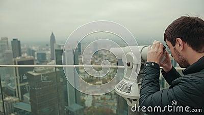 El hombre mira a través del monóculo de dispositivo de aumento en el paisaje urbano de una gran ciudad metrajes