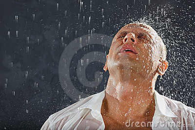 El hombre que desgasta la camisa mojada se coloca en lluvia