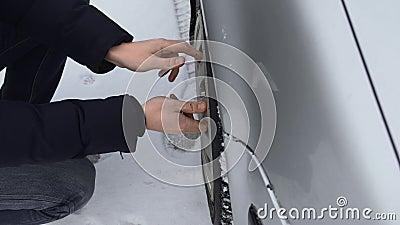 El hombre quita una tapa de ruedas de plástico de casquillo de su auto en invierno, día Tiempo malo y frío Cerrar Mal funcionamie almacen de video