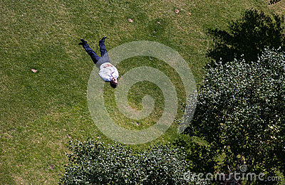 El hombre toma el sol en un parque en Londres central Imagen editorial