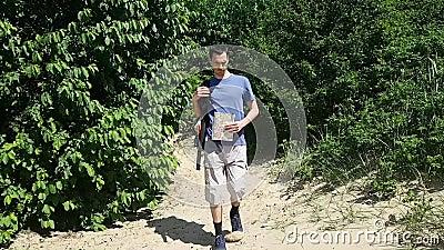 El hombre turístico cansado del viajero sale lentamente del bosque en la arena, miradas en el mapa y va al lado almacen de video