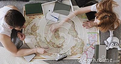 El hombre y la mujer están planeando vacaciones usando un mapa del mundo y otros accesorios del viaje almacen de video