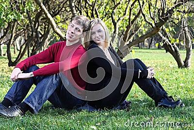 El hombre y la mujer se sientan en hierba de nuevo a la parte posterior y a sueños en parque