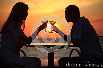 El hombre y la mujer tintinean los vidrios en puesta del sol afuera