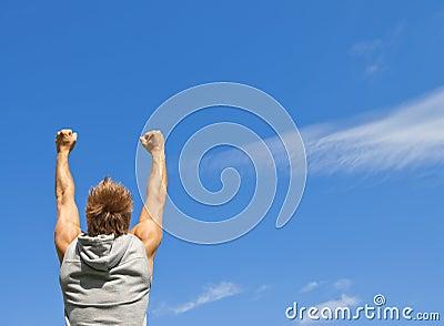 El individuo deportivo con sus brazos levantó en alegría