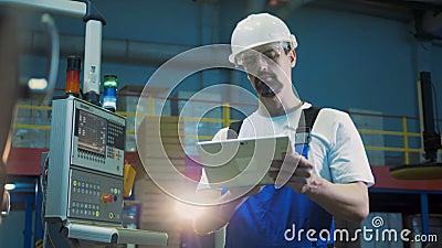 El ingeniero de sexo masculino con una tableta está trabajando al lado del panel de potencia metrajes