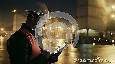 El ingeniero en el casco de protección con una tableta mira el camión en fábrica de la industria pesada almacen de video
