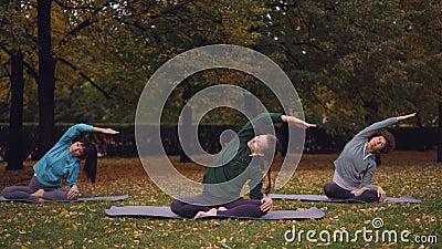 El instructor de sexo femenino de la yoga está mostrando estirando los ejercicios entonces que se relajan en la posición de loto  metrajes