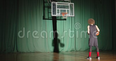 El jugador de baloncesto rizado mira a la canasta sostiene que la pelota prepara la confianza solo la sombra el rayo brillante ju almacen de metraje de vídeo