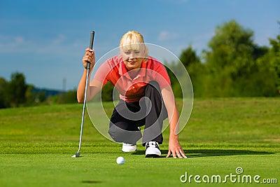 Jugador de golf femenino joven en el curso que apunta para puesto