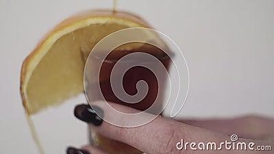 El líquido de Brown se está vertiendo sobre el vidrio con el limón sostenido por la mano de la mujer almacen de metraje de vídeo