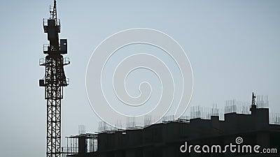 El lapso de tiempo de las grúas de torre en un lugar de construcción eleva la carga en un edificio de altura almacen de metraje de vídeo