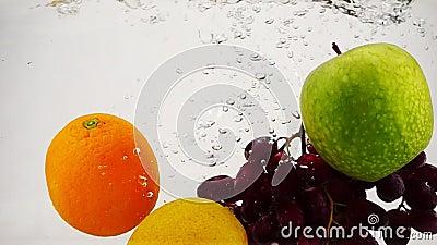 El limón, la manzana, el naranja y las uvas caen en agua con burbujas a cámara lenta. Frutas en un fondo blanco aislado metrajes
