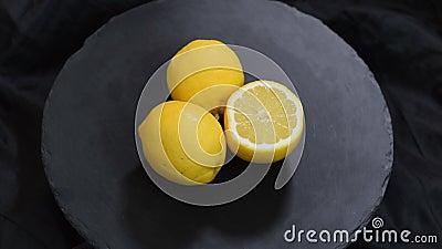 El lim?n amarillo jugoso fresco maduro en un fondo negro gira metrajes