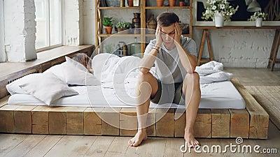 El marido infeliz se está sentando en cama después de lucha con su esposa que toca su cara y lsighing mientras que está mintiendo almacen de video