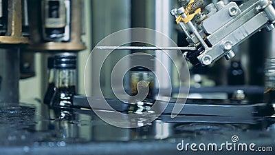 El mecanismo de la fábrica está poniendo los casquillos sobre las botellas de vidrio almacen de video