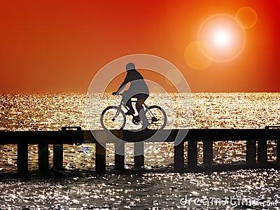 El montar en bicicleta en la puesta del sol
