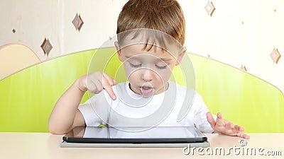 El muchacho del niño que se sienta en la tabla toca la visualización electrónica de la tableta Un niño está jugando con un ordena metrajes