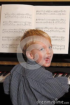 El muchacho joven juega el piano
