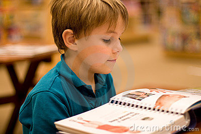 El muchacho lee un libro en la biblioteca