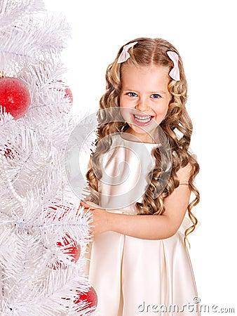 El niño adorna el árbol de navidad.