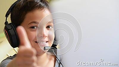 El niño feliz escucha música y jugando en el ordenador con los auriculares al aire libre almacen de metraje de vídeo