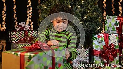 El niño lindo abre el regalo de Navidad metrajes