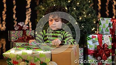 El niño lindo abre el regalo de Navidad almacen de metraje de vídeo