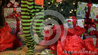 El niño lindo baila emocionado delante del árbol de navidad almacen de video