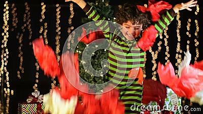 El niño lindo lanza el papel de embalaje de la Navidad en el aire almacen de metraje de vídeo